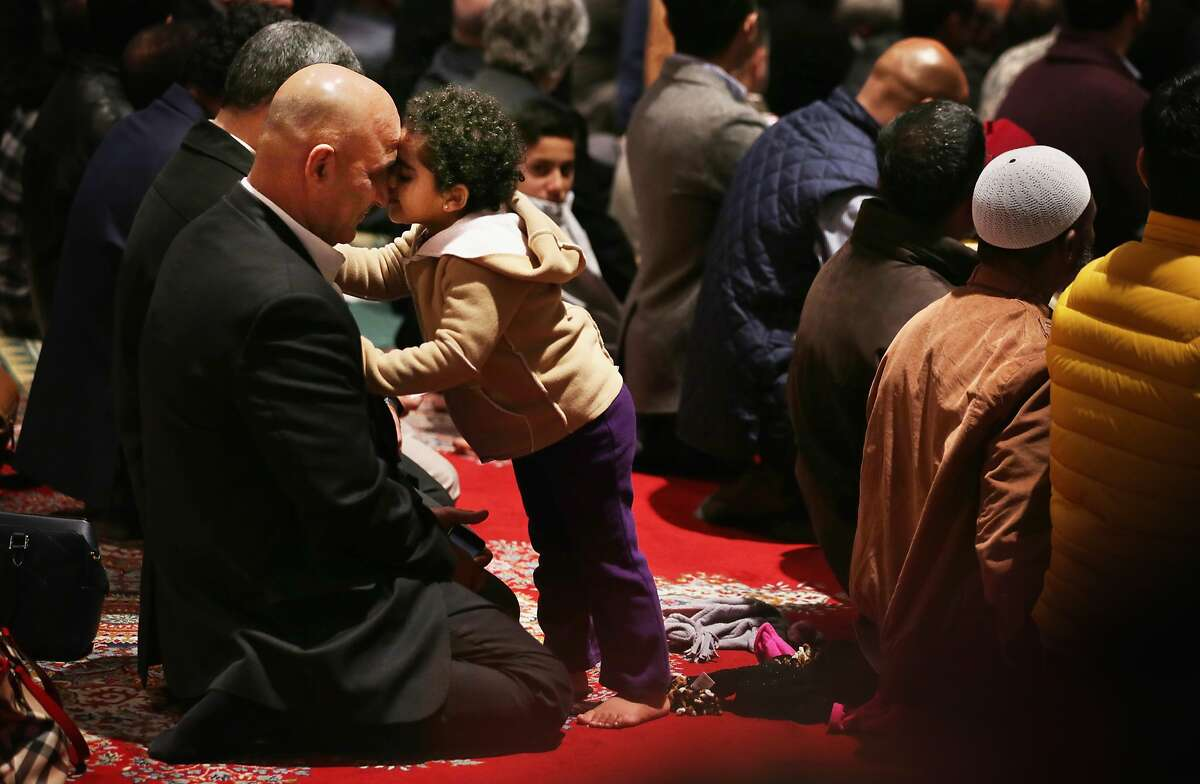 WASHINGTON, DC - NOVEMBER 14: Two-year-old Sona Agha of Burke, Virginia, shares a moment with her father Agha Hasnain during a Friday prayer November 14, 2014 at the National Cathedral in Washington, DC. Members of five Muslim communities joined the very first Muslim Friday prayer, also known as jumu'ah, that held at the cathedral today. (Photo by Alex Wong/Getty Images) *** BESTPIX ***