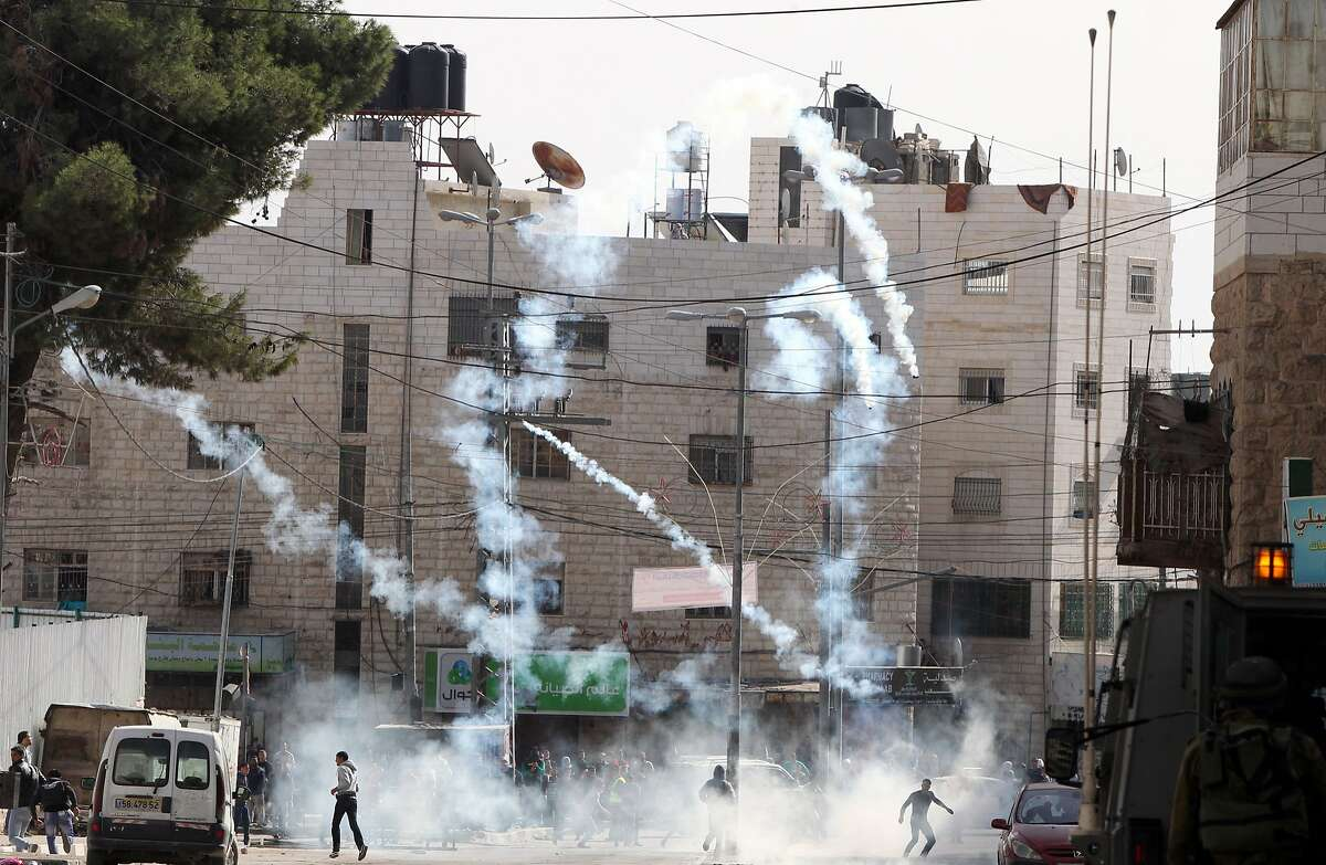 TOPSHOTS Palestinian protestors run for cover from tear gas canisters fired by Israeli security forces during clashes in the West Bank city of Hebron following a demonstration in support of Palestinians entering the Al-Aqsa mosque compound in Jerusalem for Friday prayers on November 14, 2014. Israel eased restrictions at Jerusalem's Al-Aqsa mosque on Friday after US Secretary of State John Kerry announced agreement on steps to reduce tensions at the flashpoint compound. AFP PHOTO/ HAZEM BADERHAZEM BADER/AFP/Getty Images