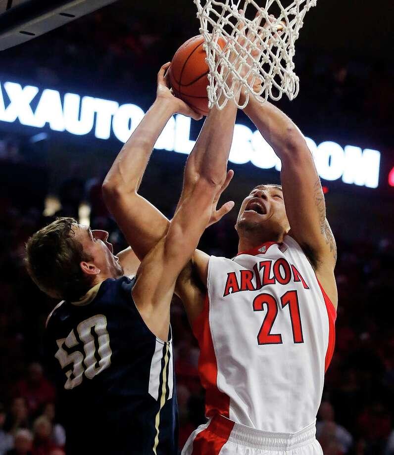 Arizona forward Brandon Ashley (21) draws the foul by Mount St. Mary's center Taylor Danaher (50) during the second half of an NCAA college basketball game, Friday, Nov. 14, 2014, in Tucson, Ariz. (AP Photo/Rick Scuteri) Photo: Rick Scuteri / Associated Press / FR157181 AP