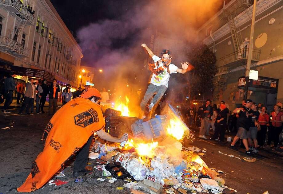 A man jumps over a pile of burning trash in San Francisco's Mission district in California after the San Francisco Giants beat the Kansas City Royals in the World Series on October 29, 2014. A celebratory mood set the stage for what eventually became a scene of bottle throwing, vandalism, and bonfires throughout the area. Photo: Josh Edelson, AFP/Getty Images