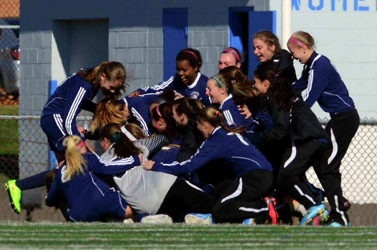 Immaculate teammates pile onto each other after beating Avon, during Class L CIAC state girls soccer championship action in West Haven, Conn. on Saturday Nov. 15, 2014.