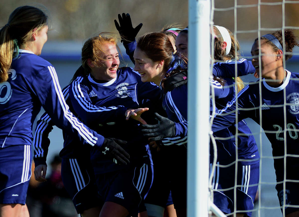 Immaculate teammates surround Paige Davis, center, after scoring the tie-breaking goal against Avon, during Class L CIAC state girls soccer championship action in West Haven, Conn. on Saturday Nov. 15, 2014.