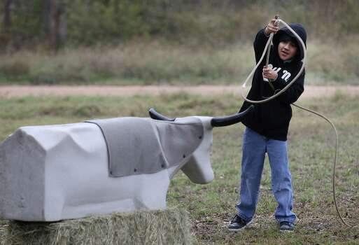 Shawn Espinoza, 10, attempts to lasso a prop animal during Farm Day at Mission San Juan on Saturday, Nov. 15, 2014. Farm Day featured various activities for guests to learn about how agriculture at the mission took root. Docents and National Park Service personnel showed various aspects of life at the mission that involved farming, raising animals and the development of an irrigation system. One of the highlights was a tour of the working acequia that is currently used to irrigate land around the mission as officials hope to grow and harvest crops on the land. Photo: Kin Man Hui, San Antonio Express-News / ©2014 San Antonio Express-News