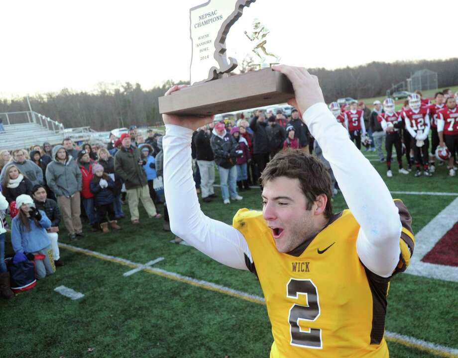 Brunswick School quarterback Billy O'Malley hoists the NEPSAC Wayne Sanborn Bowl Championship trophy above his head at the conclusion of the high school football game between Brunswick School and Governor's Academy at Avon Old Farms School, Avon, Conn., Saturday afternoon, Nov. 15, 2014. Brunswick defeated Governor's Academy, 46-20, to take the bowl. Photo: Bob Luckey / Greenwich Time