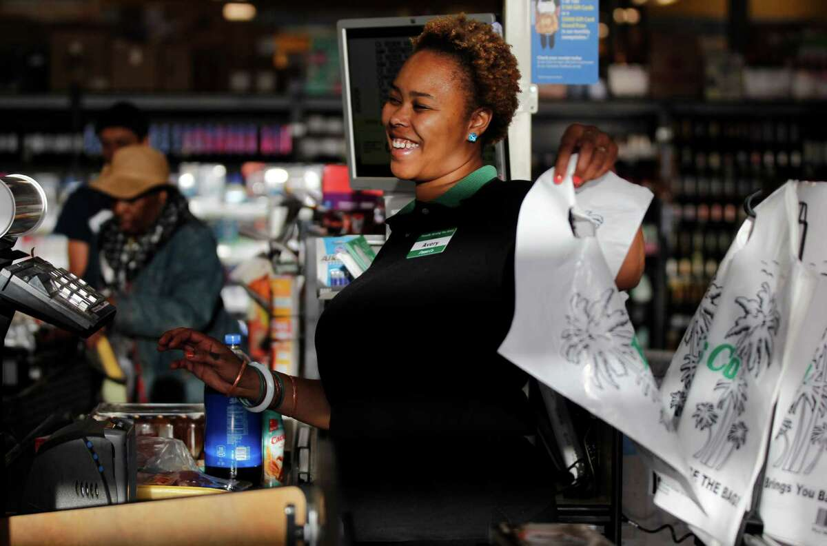 Employee Avery Dollar gives a customer a plastic bag in Foods Co Nov. 14, 2014 in Oakland, Calif.