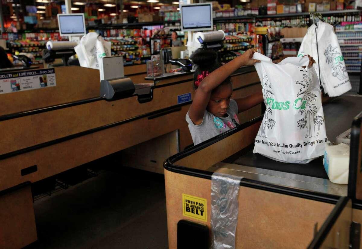 Kiara Patrick, 7, helps her mother bag up their groceries in Foods Co Nov. 14, 2014 in Oakland, Calif.