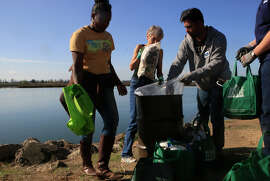 Lakisha Mitchell-Mellor (left), restoration ecologist with the Golden Gate Audubon Society, works with volunteers Diana Mueller, Kavi Lal and Nathan Weaver at the monthly cleanup on the Oakland shoreline.