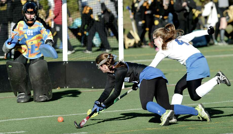 Darien's Georgia Cassidy (2) sends the ball across the front of the Glastonbury goal as time runs out in the 2nd overtime of the 2014 CIAC Girls Field Hockey Class L Championship game between Glastonbury and Darien high schools, played at Wethersfield High School, Wethersfield, Conn, on Saturday, November 15, 2014. Defending are Glastonbury's Bryn Murray (4) and goalie Marie Casey (01).  Both schools were named co-champions after two score less overtimes ending in a 1-1 tied game. Photo: H John Voorhees III / The News-Times