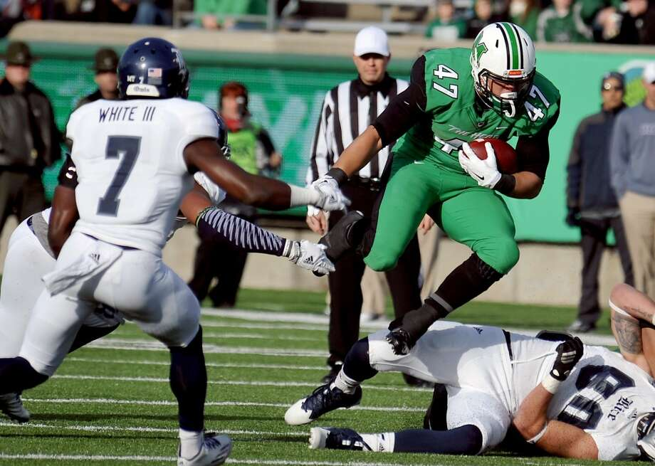 Nov. 15: No. 21 Marshall 41, Rice 14Record: 6-4 Marshall's Devon Johnson (47) leaps over a Rice defender during an NCAA football game in Huntington, W.Va., Saturday, Nov. 15, 2014. Photo: Chris Tilley, Associated Press