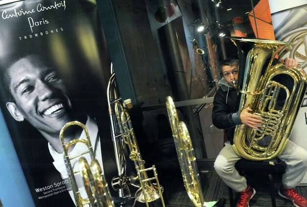Fifteen-year-old Jason Sindoni of Guilderland tries out a tuba during the John Keal Music Company sponsored professional music instrument fair as representatives from major manufacturers Yamaha, Conn-Selmer, Buffet Group, and Jupiter were on hand with dozens of top-level brand instruments direct from the factory in the Fenimore Room at Proctors on Saturday Nov. 15, 2014 in Schenectady, N.Y. (Michael P. Farrell/Times Union) Photo: Michael P. Farrell / 00029421A