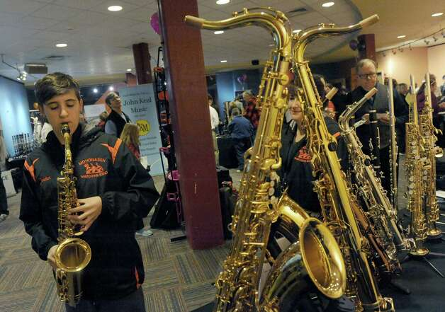 Fourteen-year-old Jordon Perez, left, a member of the Mohonasen Marching Band tries out a Yamaha YAS-62 alto saxophone during the John Keal Music Company sponsored professional music instrument fair as representatives from major manufacturers Yamaha, Conn-Selmer, Buffet Group, and Jupiter were on hand with dozens of top-level brand instruments direct from the factory in the Fenimore Room at Proctors on Saturday Nov. 15, 2014 in Schenectady, N.Y. (Michael P. Farrell/Times Union) Photo: Michael P. Farrell / 00029421A