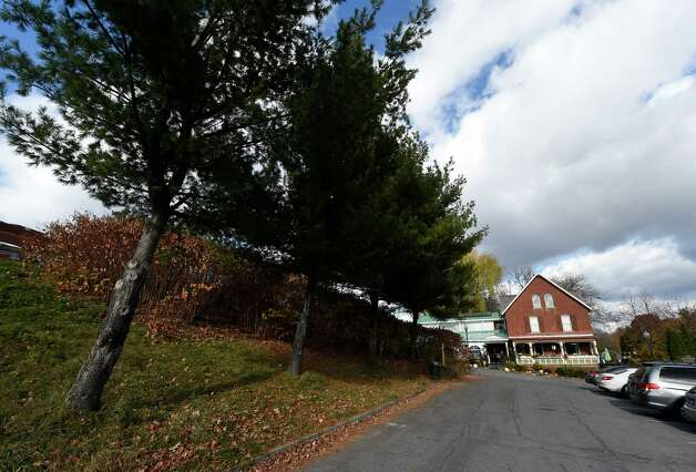 Three pine trees on the left mark the area of the proposed parking garage that would obscure the Mouzon House, right in an image made Friday afternoon Nov. 14, 2104 in Saratoga Springs, N.Y.       (Skip Dickstein/Times Union) Photo: SKIP DICKSTEIN / 00029479A