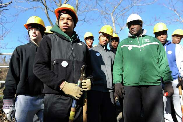 The Green Tech High varsity basketball team, including coach Jamil Hood Sr., right, prepare to cut invasive vines during a youth volunteer event on Saturday, Nov. 15, 2014, at the Corning Preserve in Albany, N.Y. With the City of Albanya€™s authorization, they cut the Oriental Bittersweet and other vines that are choking out trees in the riverfront preserve. (Cindy Schultz / Times Union) Photo: Cindy Schultz / 00029445A