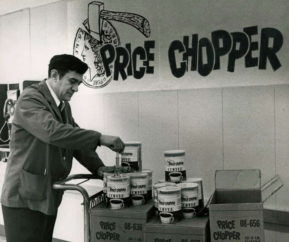 Art Ferro, assistant manager at Price Chopper supermarket on Madison Ave., stamps new prices on coffee cans Oct. 3, 1973, in Albany, N.Y. The original Price Chopper logo is shown in the background. (Times Union archive)