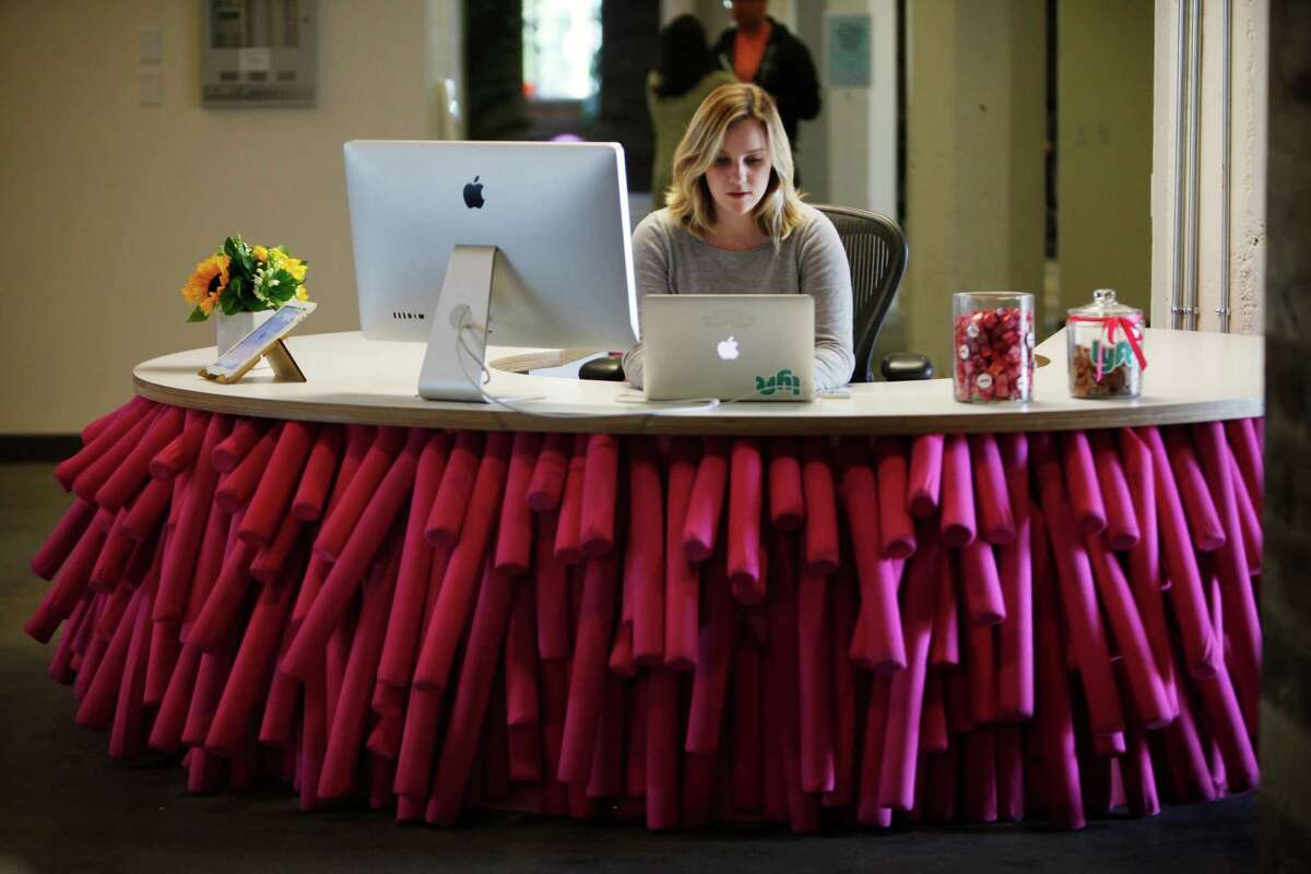 Lyft office coordinator Jen Zitterman works at a front desk decorated with pink pool noodles on Thursday, November 6, 2014 in San Francisco, Calif.