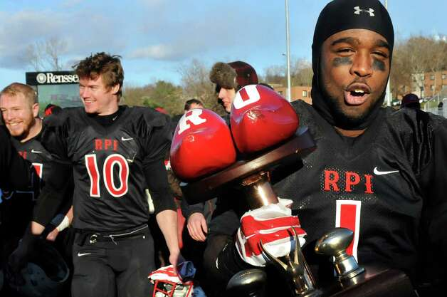 RPI's Reggie Colas, right, triumphantly carries the Dutchman Shoes Trophy after beating Union 31-28 in their football matchup on Saturday, Nov. 15, 2014, at Rensselaer Polytechnic Institute in Troy, N.Y. (Cindy Schultz / Times Union) Photo: Cindy Schultz / 00029476A