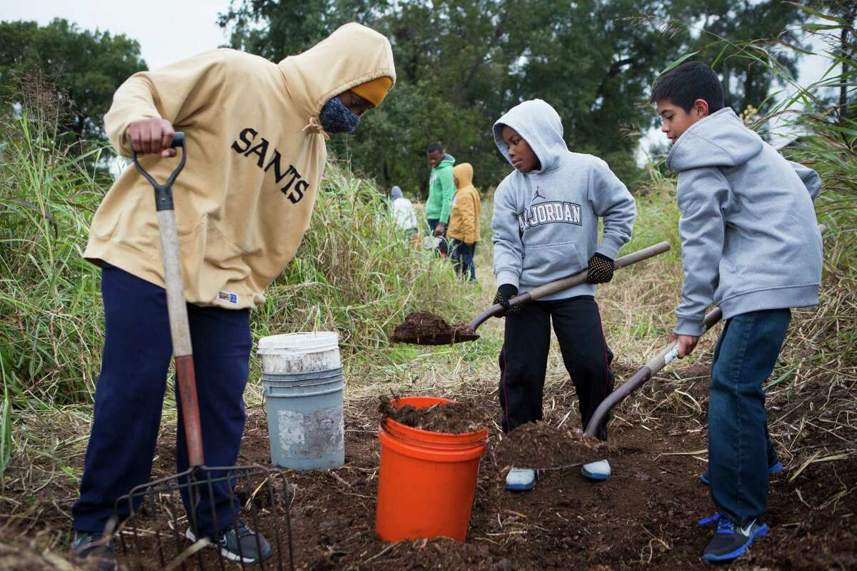 Ellington Brantley, left, 15; Dedrick Miles, center, 8; and Kyle Schooley, 10, work at the Evergreen Negro Cemetery as part of the outdoor stewardship day.