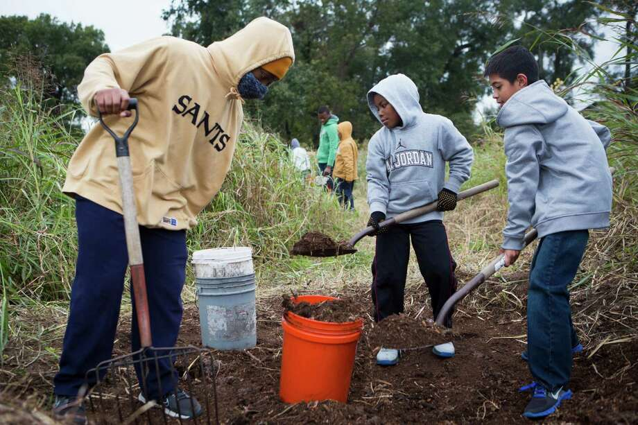 Ellington Brantley, left, 15; Dedrick Miles, center, 8; and Kyle Schooley, 10, work at the Evergreen Negro Cemetery as part of the outdoor stewardship day. Photo: Marie D. De Jesus, Staff / © 2014 Houston Chronicle