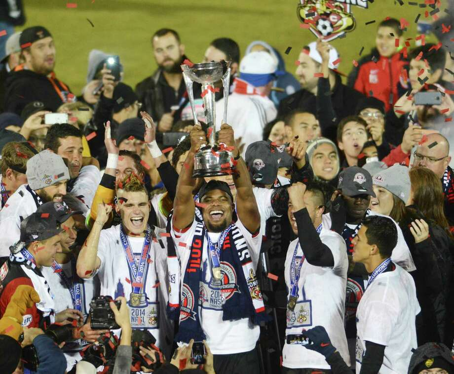 Julius James holds the NASL Championship trophy as the San Antonio Scorpions celebrate after defeating Ft. Lauderdale, 2-1, at Toyota Field on Saturday, Nov. 15, 2014. Photo: Billy Calzada, By Billy Calzada/Express News / San Antonio Express-News