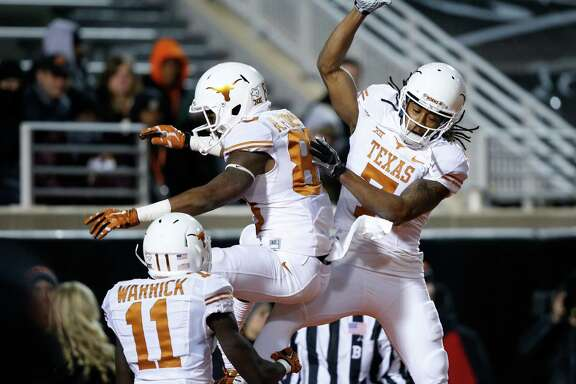 Texas wide receiver Armanti Foreman, center, celebrates his fourth-quarter touchdown with Jacorey Warrick (11) and Marcus Johnson. Foreman caught a 45-yard pass from Tyrone Swoopes to cap the scoring.