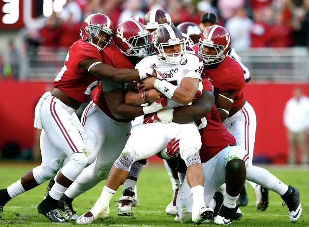 TUSCALOOSA, AL - NOVEMBER 15:  Dak Prescott #15 of the Mississippi State Bulldogs is tackled by Landon Collins #26, Dalvin Tomlinson #54 and Xzavier Dickson #47 of the Alabama Crimson Tide at Bryant-Denny Stadium on November 15, 2014 in Tuscaloosa, Alabama.  (Photo by Kevin C. Cox/Getty Images) ORG XMIT: 517299279 Photo: Kevin C. Cox / 2014 Getty Images