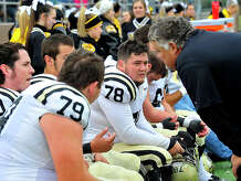 Nederland's defense, including Cameron Bullion (#78) get coaching advice in-between plays as they face Kingwood Park during their playoff game Saturday at Galena Park ISD Stadium.  Photo taken Saturday, November 15, 2014 Kim Brent/The Enterprise