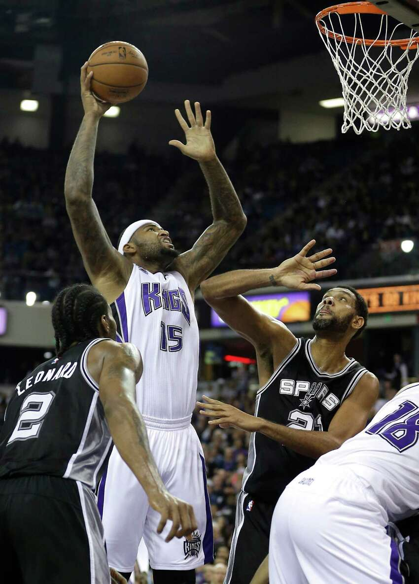 Sacramento Kings center DeMarcus Cousins, center, shoots over San Antonio Spurs forward Tim Duncan, right, as Spurs forward Kawhi Leonard watches during the second half of an NBA basketball game in Sacramento, Calif., Saturday, Nov. 15, 2014. The Kings won 94-91.