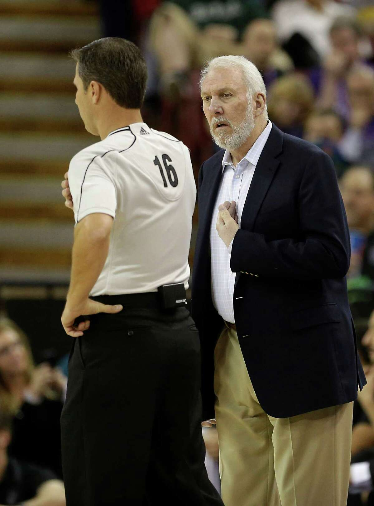 San Antonio Spurs head coach Gregg Popovich, questions Official David Guthrie about a call during the first quarter of an NBA basketball game against Sacramento Kings in Sacramento, Calif., Saturday, Nov. 15, 2014.