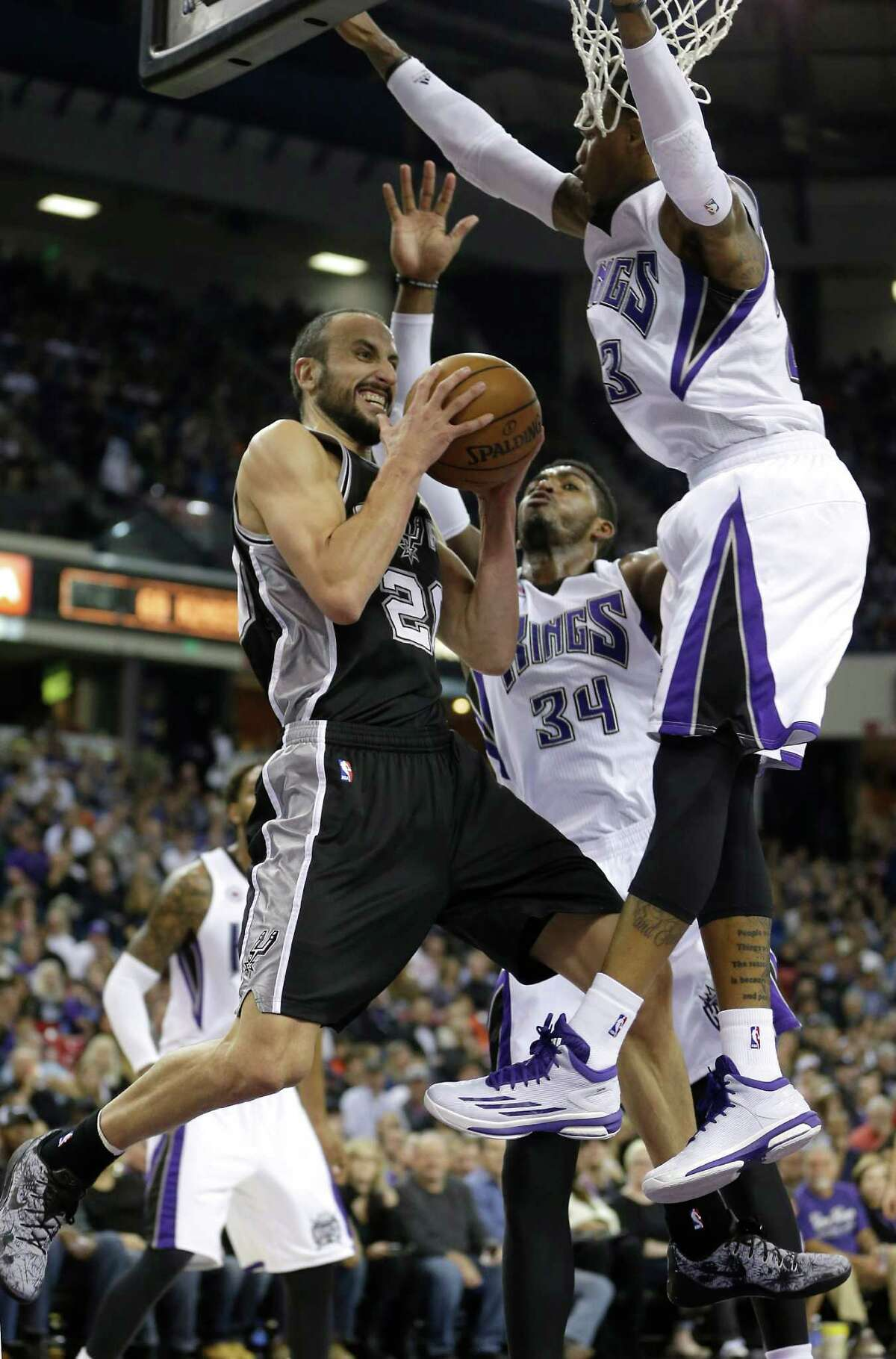San Antonio Spurs guard Manu Ginobili, of Agrentina, left, is doubled teamed by Sacramento Kings Jason Thompson, center and Ben McLemore, during the first quarter of an NBA basketball game in Sacramento, Calif., Saturday, Nov. 15, 2014.