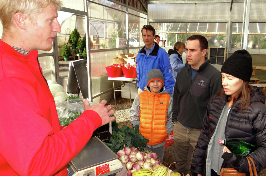 Simon Ziegler, left, of Riverbank Farm, assists Nicole Flavin, as Nicole's son, Jackson, 11, and husband, Casey, look on at the Westport Winter Farmers Market's opening Saturday at Gilbertie's Herb Gardens. Photo: Mike Lauterborn / Westport News