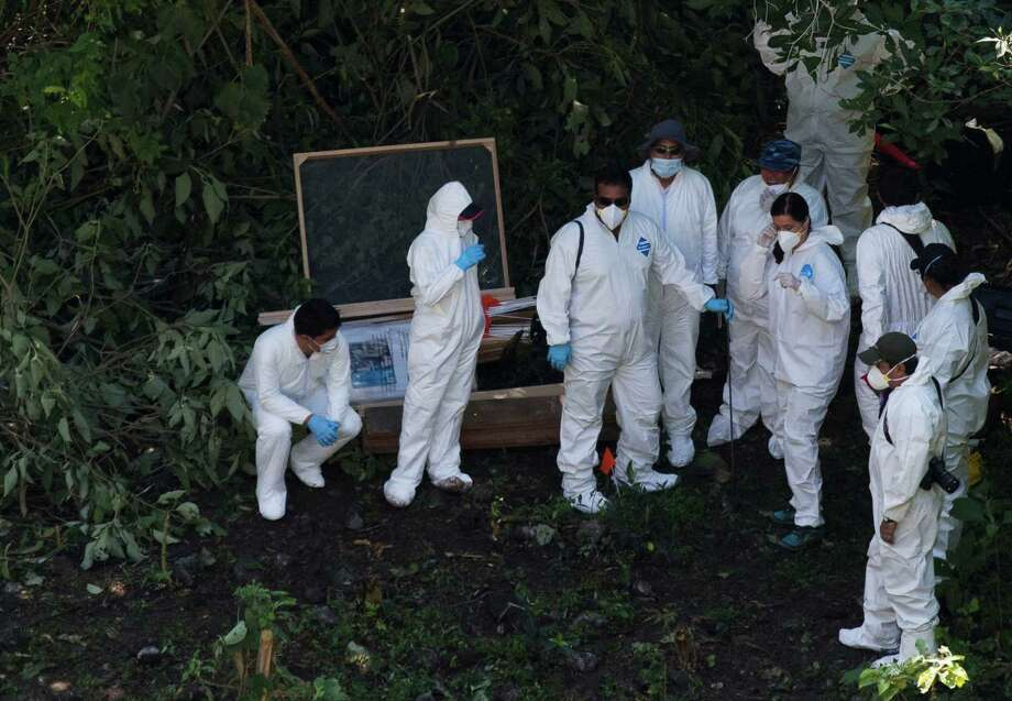 FILE - In this Oct. 28, 2014 file photo, forensic examiners coordinate as they search for human remains below a garbage-strewn hillside in the densely forested mountains outside Cocula, in Guerrero state, Mexico. Over time, 10,000 federal agents and dozens of forensics investigators in hazmat suits joined the search, and a reward was offered for information on the 43 missing rural college students. Arrests were made --74 in all. But Mexicans grew incredulous when investigators couldn�t find the missing students. Photo: Rebecca Blackwell, AP / AP