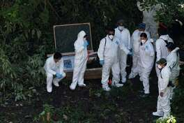 FILE - In this Oct. 28, 2014 file photo, forensic examiners coordinate as they search for human remains below a garbage-strewn hillside in the densely forested mountains outside Cocula, in Guerrero state, Mexico. Over time, 10,000 federal agents and dozens of forensics investigators in hazmat suits joined the search, and a reward was offered for information on the 43 missing rural college students. Arrests were made --74 in all. But Mexicans grew incredulous when investigators couldn�t find the missing students.