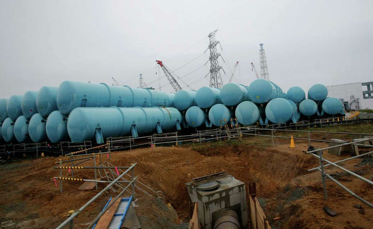 Water tanks that store contaminated water are seen at the Fukushima Dai-ichi nuclear power plant in Okuma, Fukushima prefecture, northeastern Japan, Wednesday, Nov. 12, 2014. Nearly all the workers at the Fukushima Dai-ichi plant are devoted to a single, enormously distracting problem: coping with a still-growing amount of contaminated water that has been used to keep the damaged reactors from overheating, and whose volumes are swelled by groundwater that is getting into the reactor buildings. A number of buildings housing water treatment machines and hundreds of huge blue- and gray-colored industrial tanks to store the excess water are rapidly taking over the plant, which saw three of its six reactors melt down following the 2011 earthquake and tsunami.