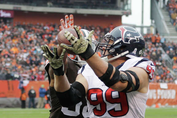 Houston Texans defensive end J.J. Watt (99) catches a touchdown pass against Cleveland Browns inside linebacker Christian Kirksey (58) in the first quarter of an NFL football game Sunday, Nov. 16, 2014, in Cleveland. (AP Photo/Tony Dejak)