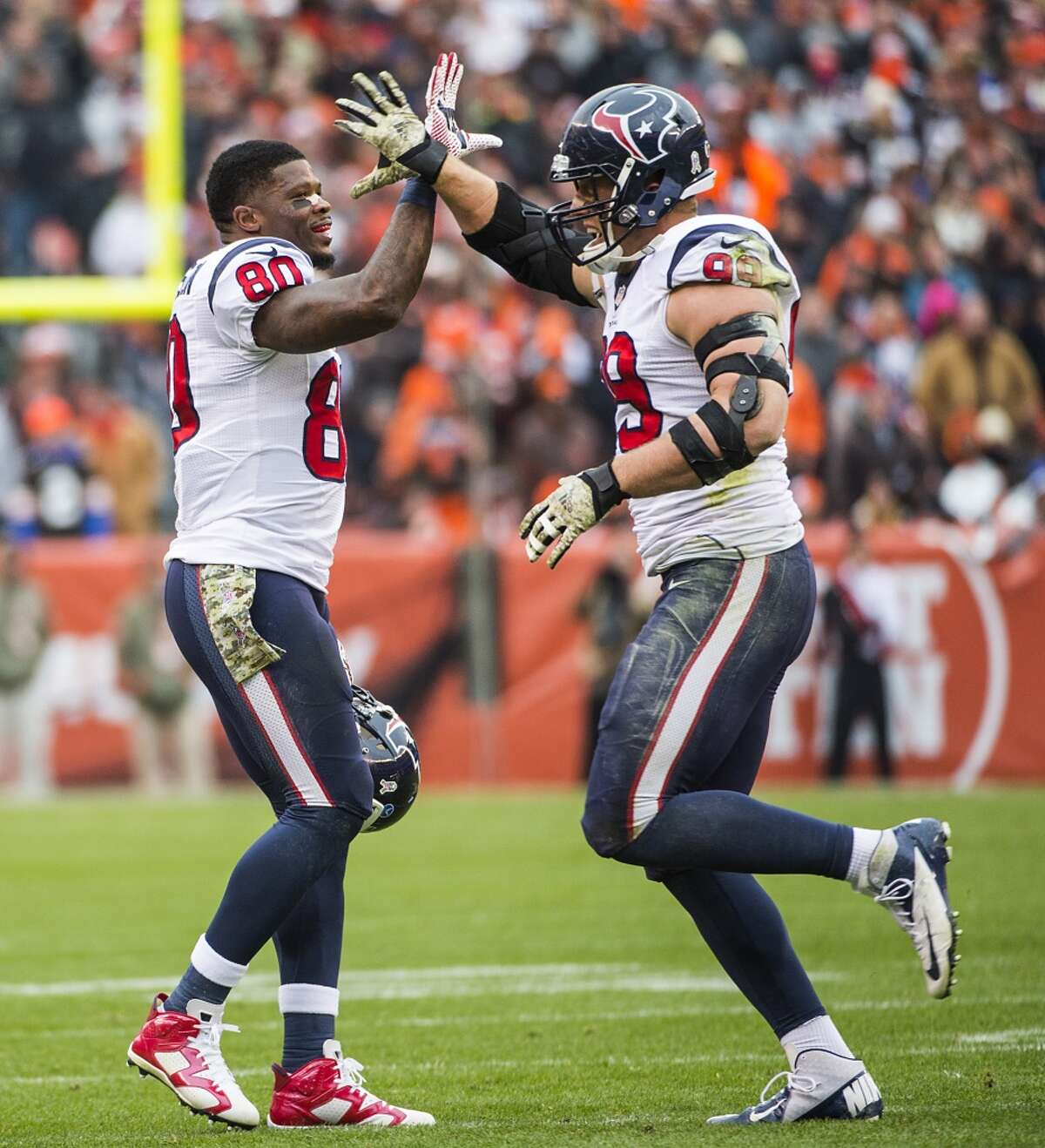 Houston Texans defensive end J.J. Watt (99) gets a hand from wide receiver Andre Johnson (80) after scoring on a touchdown pass during the first quarter of NFL football game against the Cleveland Browns at FirstEnergy Stadium on Sunday, Nov. 16, 2014, in Cleveland. ( Smiley N. Pool / Houston Chronicle )