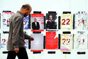 Flyers for presidential candidates line the walls in Tunis.