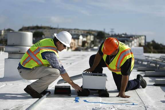 Chris Paras (l to r), utility specialist PUC, talks with Doug Joya, electrician DPW,  look in a combiner box on the roof of  Thurgood Marshall Academic High School which will be connected to the solar panels (partially seen at right) being installed on the roof on Friday, November 14, 2014 in San Francisco, Calif.