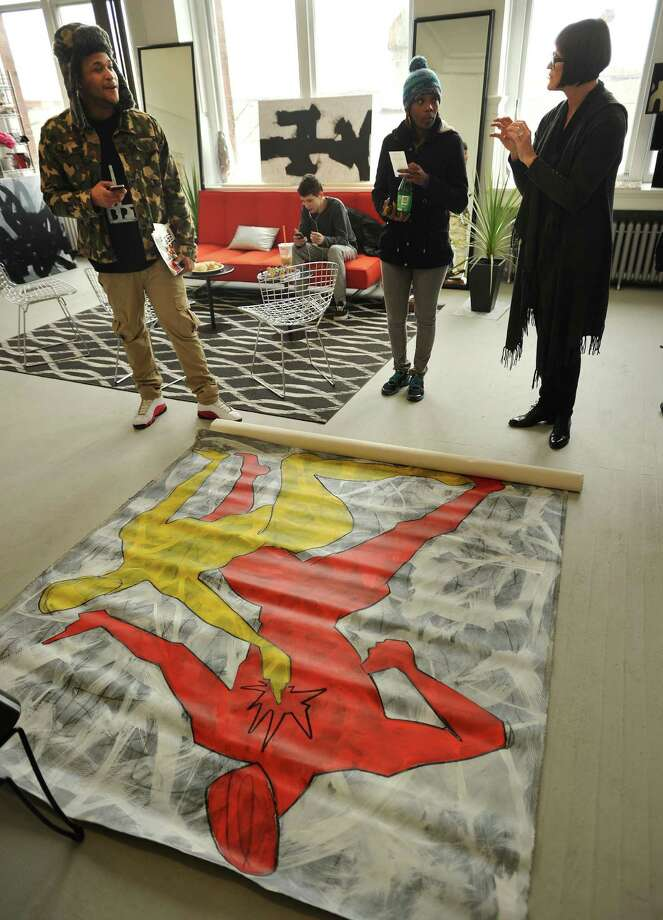 Artist Ayn Kraven, right, of Westport, shows one of her large scale, abstract, acrylic paintings to Henry Reyes and DeAndrea Hinds, both of Bridgeport, during the 6th Annual Bridgeport Art Trail city-wide open studio weekend at the former American Fabrics factory artists' studios at 1069 Connecticut Avenue in Bridgeport, Conn. on Sunday, November 16, 2014. Photo: Brian A. Pounds / Connecticut Post