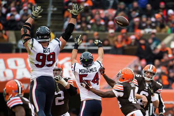Texans defensive end J.J. Watt (99) and inside linebacker Mike Mohamed (54) put up a wall of hands and bat down a pass by Browns quarterback Brian Hoyer (6). The Texans' run defense forced Hoyer to pass more than he wanted. Mohamed also had an interception.