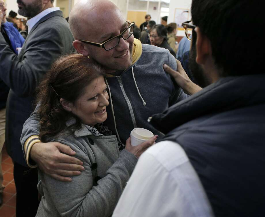 Rafael Mandelman hugs Tami Bryant, left, at a reception following a memorial for Ted Gullicksen on Sunday at Mission High School. Friends and family of Ted Gullicksen, a long-time San Francisco housing rights activist, gathered at Mission High School in San Francisco, Calif., to honor him at a memorial service on Sunday, November 16, 2014. Photo: Carlos Avila Gonzalez, The Chronicle