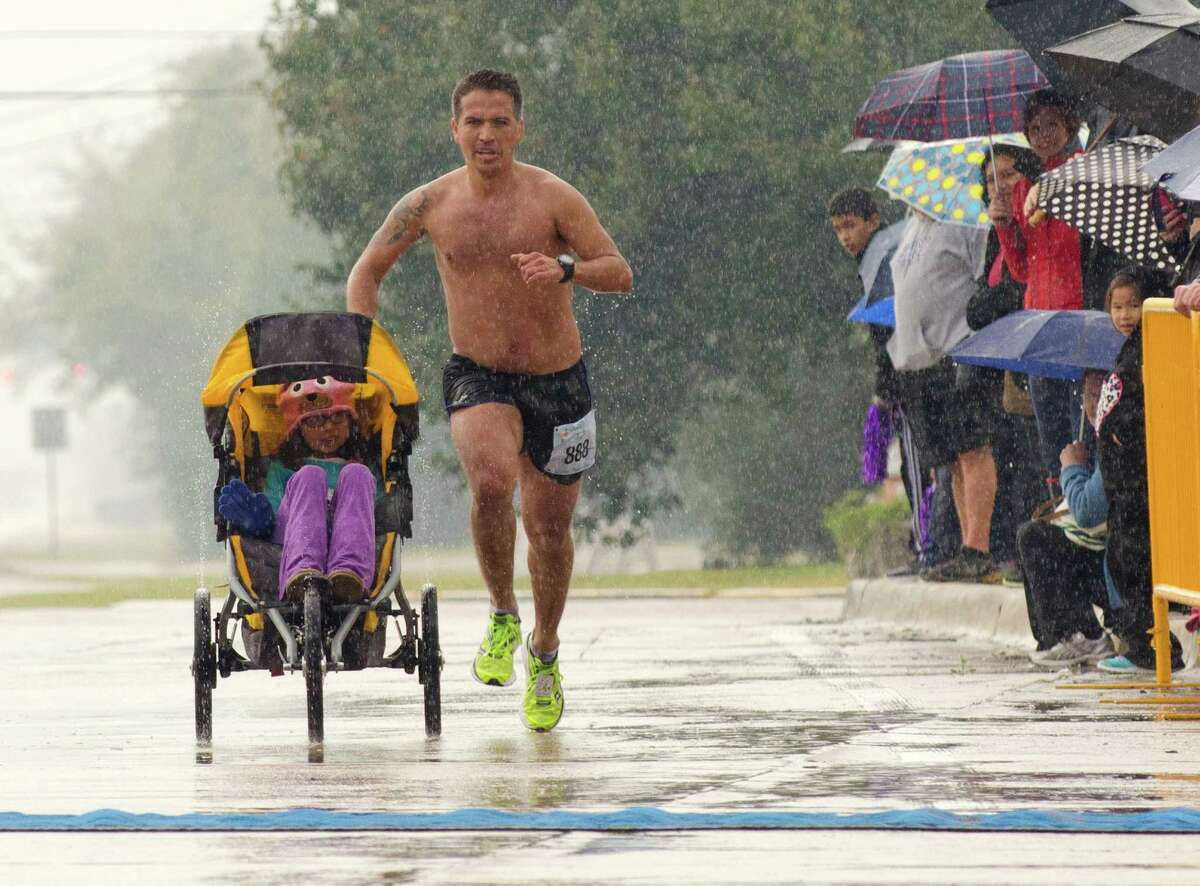 Iram Leon, 34, nears the finish line of the La Porte by the Bay Half Marathon in 10th place while pushing his daughter Kiana, 7, in a jogging stroller Sunday in La Porte. Leon, from Austin, was diagnosed with terminal brain cancer four years ago.