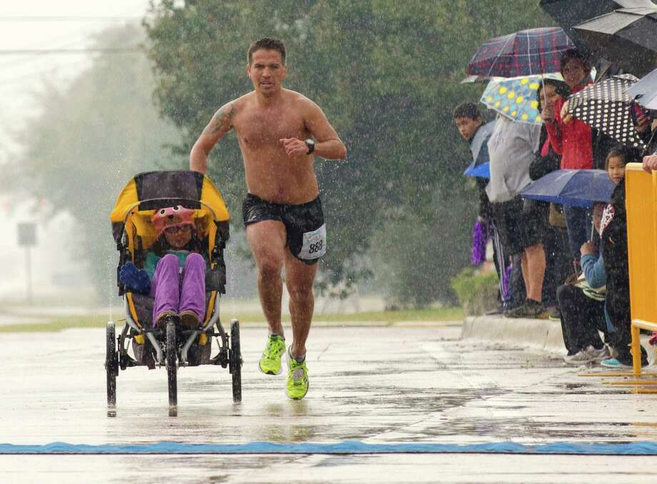 Iram Leon, 34, nears the finish line of the La Porte by the Bay Half Marathon in 10th place while pushing his daughter Kiana, 7, in a jogging stroller Sunday in La Porte. Leon, from Austin, was diagnosed with terminal brain cancer four years ago. Photo: Alysha Beck, Freelancer / Houston Chronicle