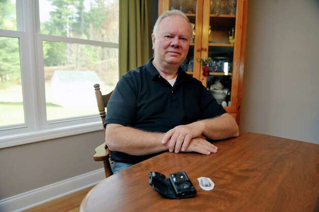 Don Womer poses with a continuous glucose monitor seen on the table at his home on Monday, Nov. 10, 2014, in Guilderland, N.Y.  The smaller device is worn on the stomach or upper arm and reads the person's glucose level every 5 minutes and sends the reading to the receiver.  The receiver can be set to sound alarms for high and low readings.  This device will no longer be covered by Womer's insurance company.  (Paul Buckowski / Times Union) Photo: Paul Buckowski / 00029411A