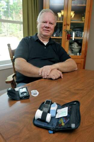 Don Womer poses with a continuous glucose monitor (on the left in photo) at his home on Monday, Nov. 10, 2014, in Guilderland, N.Y.  The smaller device is worn on the stomach or upper arm and reads the person's glucose level every 5 minutes and sends the reading to the receiver.  The receiver can be set to sound alarms for high and low readings.  This device will no longer be covered by Womer's insurance company.  Womer will have to go back to using the glucose finger stick method, using the kit seen on the right.    (Paul Buckowski / Times Union) Photo: Paul Buckowski / 00029411A