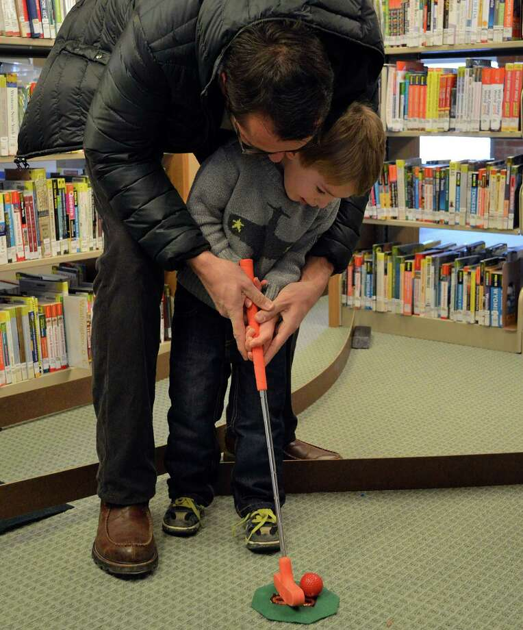 Karl Scaccia of Darien helps son Leo, 3, fine tune his form at the mini golf event Saturday at the Darien Library. Photo: Jarret Liotta / Darien News
