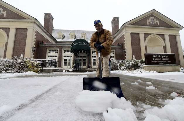State Parks, Recreation and Historic Preservation employee Evaristo Valentine shovels snow from the Hall of Springs in Saratoga Springs. (Skip Dickstein / Times Union)