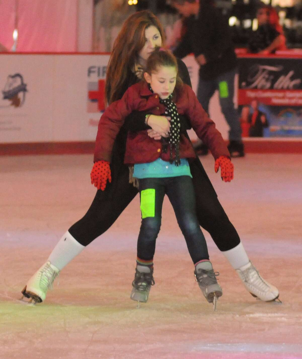Abi Legate, of The Woodlands, helps her little sister, Anna, with her skating during The Ice Rink in The Woodlands preview weekend skating. The Ice Rink is located at the northeast corner of Lake Robbins and Six Pines Drive.