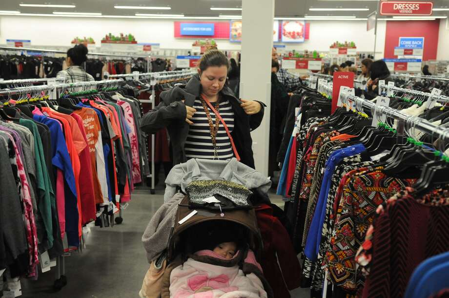 A shopper tries on new coats at the Burlington store in Copperfield during its grand opening in this file photo from Nov. 14, 2014. For the 2016 holiday shopping season, the retailer has announced it plans to hire thousands of workers nationwide. Photo: Jerry Baker, Freelance