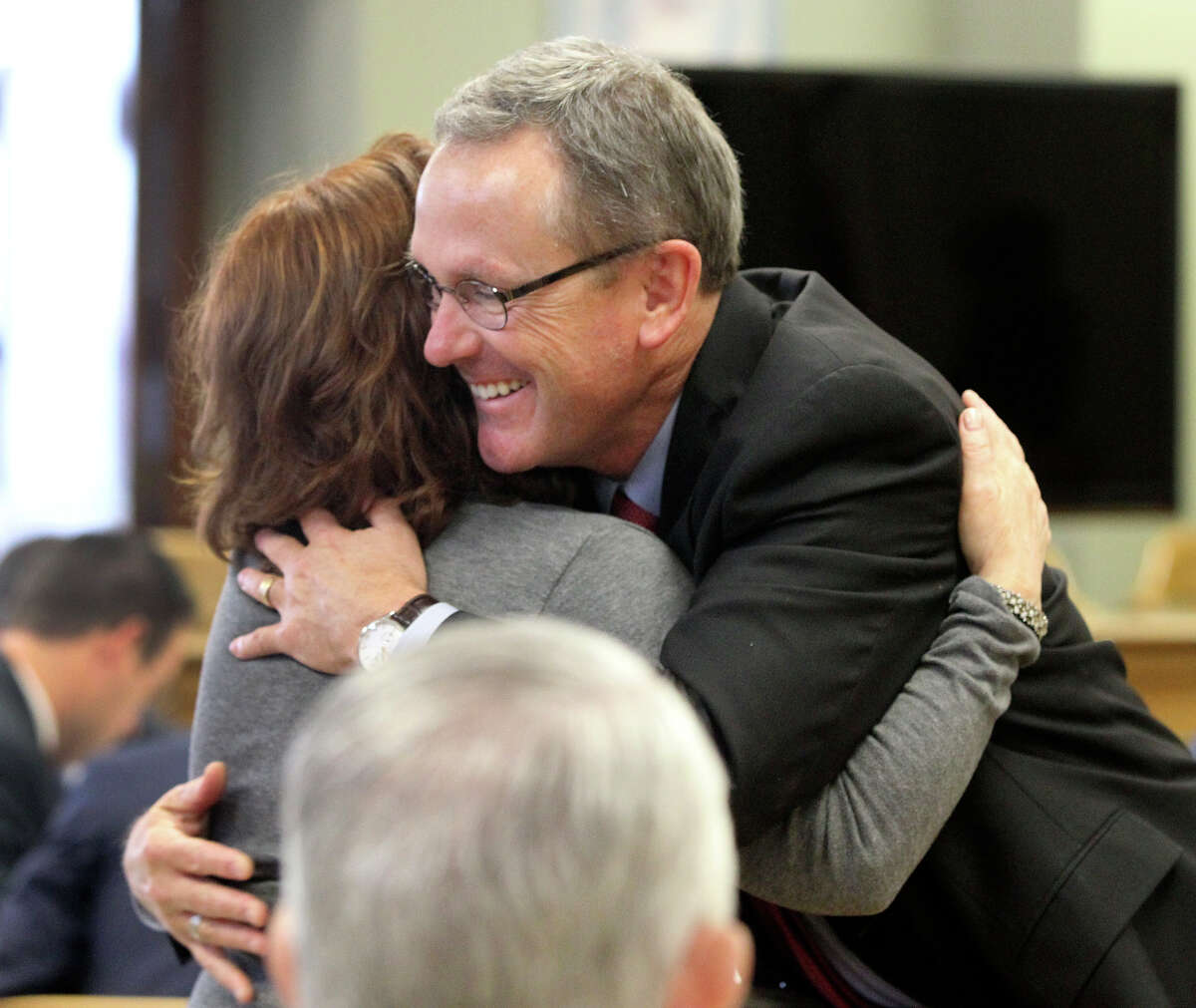 Attorney Mike McCrum (right) gets a hug from a supporter Monday November 17, 2014 in the 225th District Court at the Bexar County Courthouse during a contempt of court hearing. McCrum, serving as a special prosecutor in the case against Gov. Rick Perry, who is also accused of professional misconduct, could spend up to six months in jail if found guilty in contempt. After nearly a nine-month hiatus, the hearing resumed for McCrum.