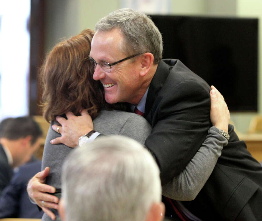 Attorney Mike McCrum (right) gets a hug from a supporter Monday November 17, 2014 in the 225th District Court at the Bexar County Courthouse during a contempt of court hearing. McCrum, serving as a special prosecutor in the case against Gov. Rick Perry, who is also accused of professional misconduct, could spend up to six months in jail if found guilty in contempt. After nearly a nine-month hiatus, the hearing resumed for McCrum. Photo: JOHN DAVENPORT, San Antonio Express-News / ©San Antonio Express-News/John Davenport